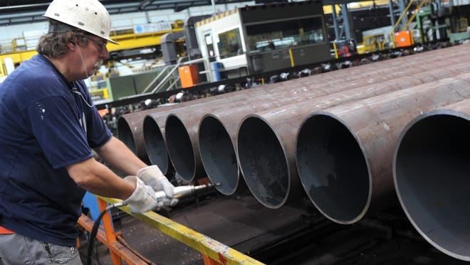 An employee checks a steel pipe in the manufacturing hall at Vallourec and Mannesmann in Dusseldorf, Germany, in  2013.