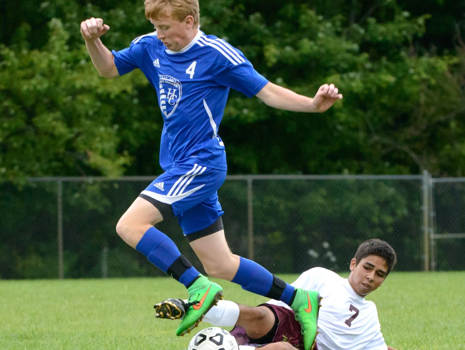 Nick Robinson (4) of Harper Creek gets tripped up by Delton Kellogg's Tristan Arce as Robinson was going for the ball.