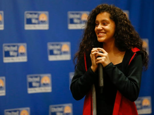 Adayah Glenn, an eighth-grader at Pipkin Middle School, smiles as the crowd applauds after she sang the national anthem at the annual United Way of the Ozarks luncheon on Wednesday, April 11, 2018.