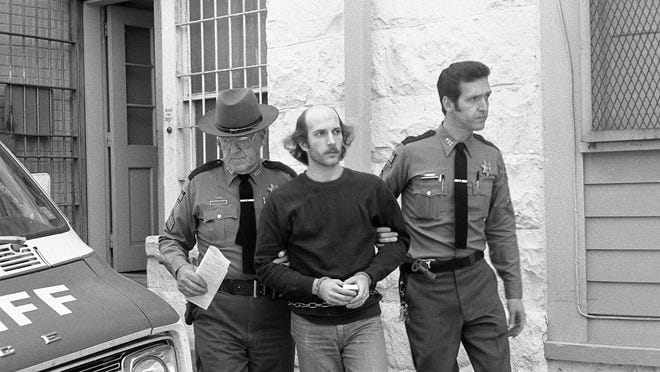 """Serge A. Motti was convicted of murdering two Putnam County women in order to steal their dog in the """"Kent kennel killings."""" Here, he is taken away to prison on a sunny day in 1979."""