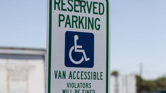 A disabled placard is displayed at the parking lot of Y-Knot Party & Rentals in Mesa as a man cleans the asphalt in preparation for restriping on July 14, 2016. The business is restriping stalls in their parking lot to meet accessibility requirements outlined by the Americans With Disabilities Act.