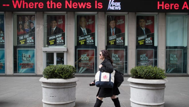 "A woman walks past the News Corp. headquarters in New York on April 19, 2017. Later that day, Fox News Channel host Bill O'Reilly was fired after an investigation into sexual harassment. In a message to employees, Rupert Murdoch and sons, James and Lachlan, who run 21st Century Fox, said the decision follows ""an extensive review done in collaboration with outside counsel."""