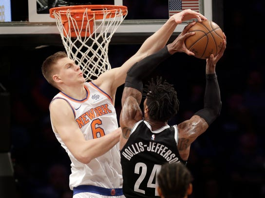 New York Knicks' Kristaps Porzingis, left, fouls Brooklyn Nets' Rondae Hollis-Jefferson during the first half of the NBA basketball game at the Barclays Center, Monday, Jan. 15, 2018 in New York. (AP Photo/Seth Wenig)