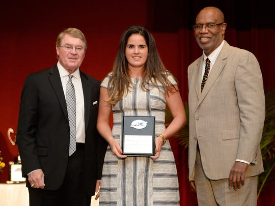 Clemson's Daniela Ruiz (center) is honored by ACC Commissioner John Swofford and Miami's Marvin Dawkins during the 2018 ACC Postgraduate Scholarship Luncheon in Greensboro, N.C., April 11, 2018.