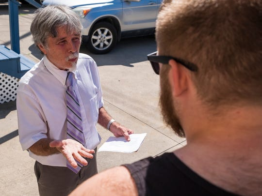 Democratic candidate Michael McCarthy speaks to Port Huron resident Jacob Hawley on Wednesday, July 18, 2018 while walking door-to-door in Port Huron.