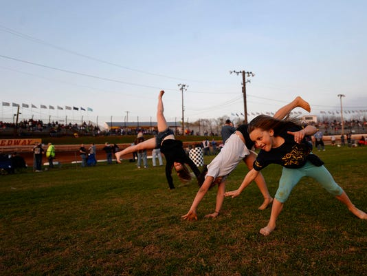"""From left Madison Tyson, 12, of Carlise, Lajaeda Pierce 8, of Mechanicsburg, MaKenna Riland 7, of Hanover, do cartwheels on the infield as cars race on the track around them at Williams Grove Speedway in Mechanicsburg Friday, April 17, 2015. Kate Penn â """" Daily Record/Sunday News"""