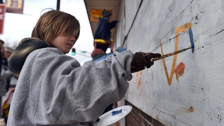 A girl paints a boarded-up storefront in Ferguson,