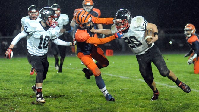 Pleasant Spartan running back Cade Lawrence uses a stiff arm to pick up yardage against the Galion Tigers defense during first-half action in high school football Friday night, Oct. 31, 2014 at Galion.