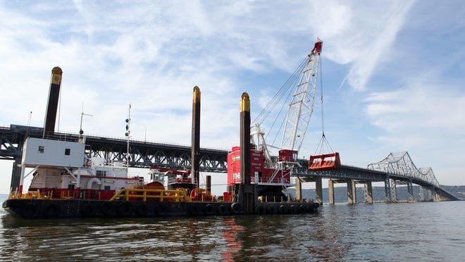 A barge carries a crane with a clamshell bucket used for dredging on Oct. 3. There are some 90 construction vessels in the river.