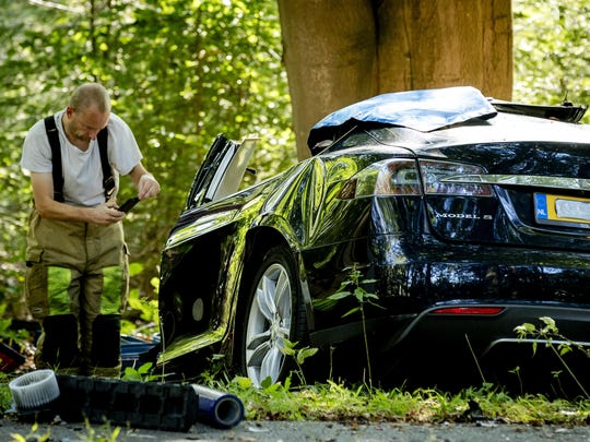 A rescue worker takes a picture around the spot where a Tesla slammed into a tree in Baarn, the Netherlands, in 2016. Driverless auto crashes has upended the risk calculation insurers rely on to set rates.