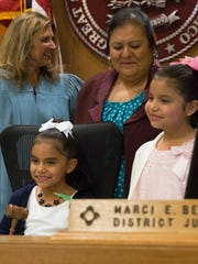 Maria Mendez,center, and her two daughters Joveigh,left and Natalie Mendez,left, pose for pictures on the Judge Marci E. Beyer's bench, after Mendez officially adopted the twins. Tuesday November 14, 2017 at the Third Judicial District Court.