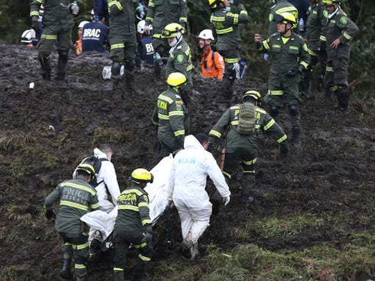 Rescue workers remove the body of a victim of an airplane crash in La Union, near Medellin, Colombia, Tuesday, Nov. 29, 2016. The plane was carrying the Brazilian first division soccer club Chapecoense team that was on it's way for a Copa Sudamericana final match against Colombia's Atletico Nacional.