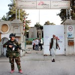 In this Oct. 15, 2015, file photo, an Afghan National Army soldier stands guard at the gate of a Doctors Without Borders hospital in Kunduz, Afghanistan. About 16 U.S. military personnel, including a two-star general, have been disciplined for mistakes that led to the bombing of the civilian hospital in Afghanistan last year that killed 42 people.