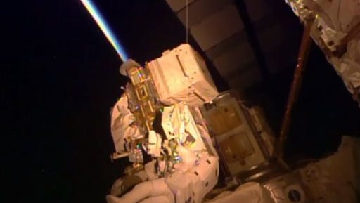 In this frame grab from NASA Television, astronaut Kjell Lindgren performs maintenance outside the International Space Station, Wednesday, Oct. 28, 2015. Lindgren and fellow astronaut Scott Kelly's to-do list included greasing the station's big robot arm, routing cables, removing insulation from an electronic switching unit and covering an antimatter and dark matter detector. (NASA via AP)