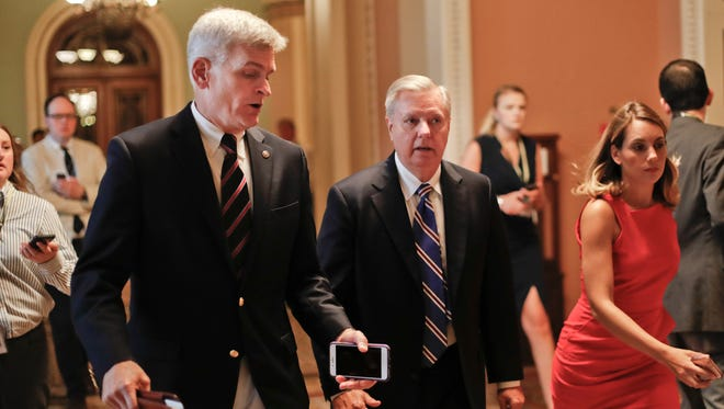 Sen. Bill Cassidy, R-La., left, and Sen. Lindsey Graham, R-S.C., right, talk while walking to a meeting on Capitol Hill on July 13, 2017.
