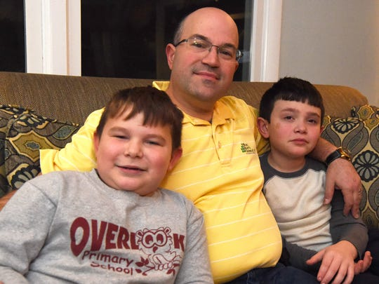Greg Spaun, center, pictured with his sons Scott, left, 6, and Stephen, right, 8, in their LaGrange home. Greg's wife Debbie died of a heart attack in September.