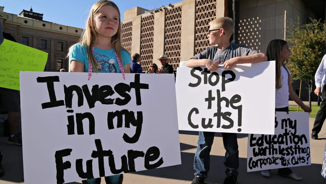John Samora/The Republic Wednesday?s education-budget protest included teachers, parents and students. Siblings, Ashley Kistner,6 Justin Kistner, 10, and Natalie Kistner, 8, hold signs during a protest against Governor Ducey's proposed educational budget cuts at the state capital. Their mother, Brooke Kistner, was one of the rally's organizers as seen in Phoenix on Feb., 25, 2015