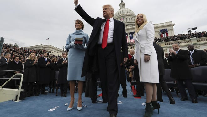 President Donald Trump acknowledges the audience after taking the oath of office as his wife, Melania, left, and daughter Tiffany watch during inauguration ceremonies.