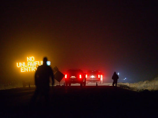 SUVs proceed through the Narrows roadblock near Burns,