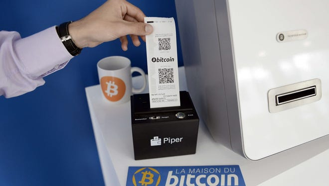 A man takes a receipt from a bitcoin (virtual currency) dispenser at La Maison du Bitcoin in Paris on June 20, 2014.