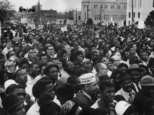 """Civil rights protesters in Montgomery after their march from Selma to protest against voter registration laws in the state on March 29, 1965. One marcher is wearing a hat with the slogan """"Freedom Now!"""" written on it."""
