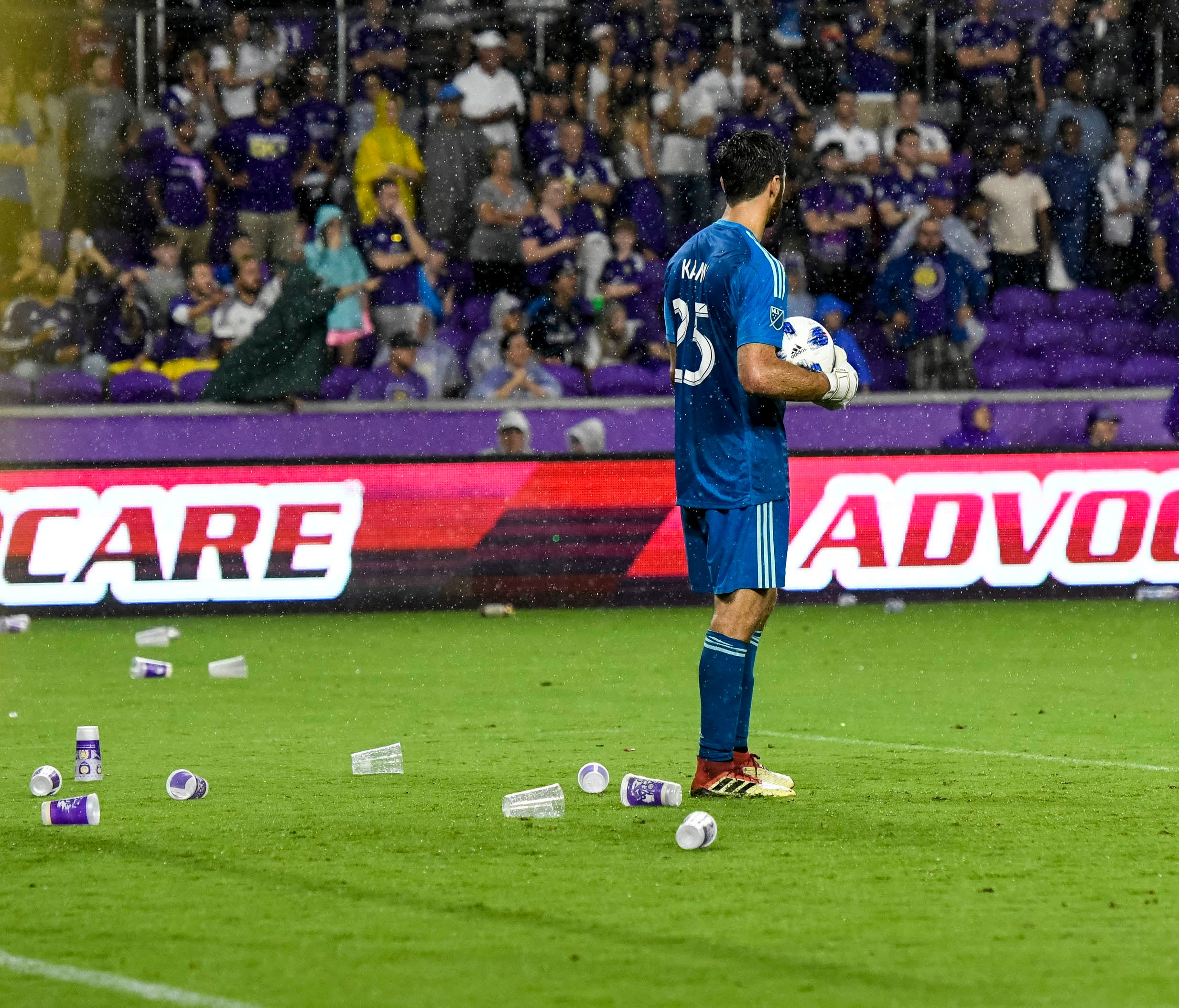 Atlanta United goalkeeper Alec Kann stands on the field as fans throw trash from the stands.