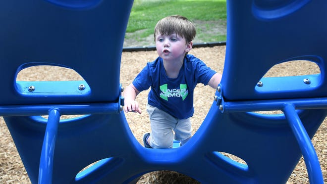 Jax Bechtol, 3, climbs for the top at the playground at Navarre-Bethlehem Township Community Park.