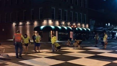 Volunteers help re-paint the checkered flag intersection at Franklin and Fourth streets in Watkins Glen before race weekend.
