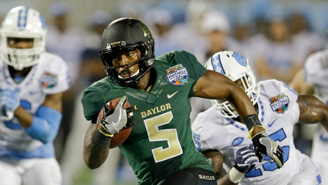 Baylor running back Johnny Jefferson (5) runs past North Carolina cornerback M.J. Stewart (6) and safety Donnie Miles, right, for a 27-yard touchdown run during the first half of the Russell Athletic Bowl.