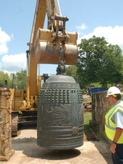 The 8,250-pound International Friendship Bell is moved back onto a concrete platform overlooking A.K. Bissell Park in Oak Ridge, where it will remain while a citizens' group works to create and fund a replacement structure for housing and hanging it. (BOB FOWLER/NEWS SENTINEL)
