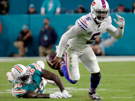 FILE - In this Sunday, Dec. 31, 2017, file photo, Buffalo Bills quarterback Tyrod Taylor (5) escapes a tackle by Miami Dolphins defensive end Andre Branch (50), during the first half of an NFL football game in Miami Gardens, Fla. The Jaguars, Bills and Titans all ended long droughts to return to the playoff party. (AP Photo/Lynne Sladky, File)