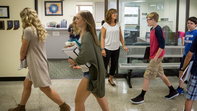 Katie Preston, the soul counselor at Yorktown Middle School, helps students find classes and deal with their lockers Friday on the first day back to school. Preston balances multiple roles including district test coordinator and schedule builder.