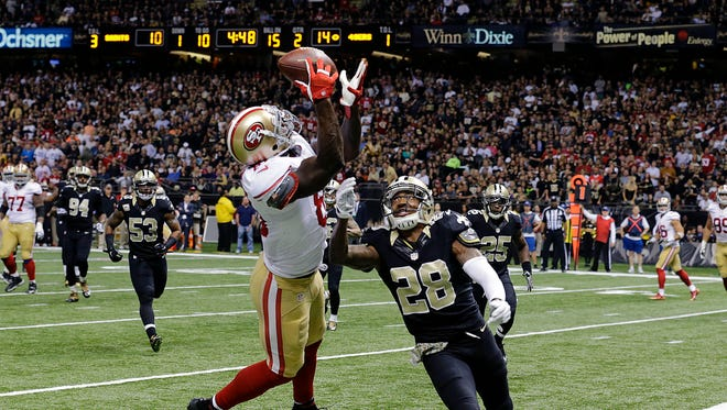San Francisco 49ers' wide receiver Anquan Boldin (left) pulls in a touchdown reception in front of New Orleans Saints' cornerback Keenan Lewis (28) in the 49ers' 27-24 win in overtime Sunday. Lewis injured his left knee trying to break up a pass to Boldin.