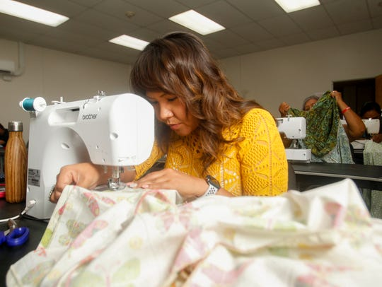 Jaime Begay of Coalmine Canyon, Arizona, works on a skirt Sunday during a skirt-making workshop hosted by the Office of Miss Navajo Nation and the Navajo Cultural Arts Program at Diné College's north campus in Shiprock.