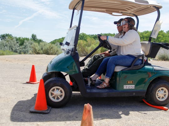 Amber Hale operates a golf cart while using impairment goggles, Thursday, July 19, during the inaugural Realtor Rally hosted by the San Juan County Board of REALTORS at the Farmington Museum at Gateway Park.