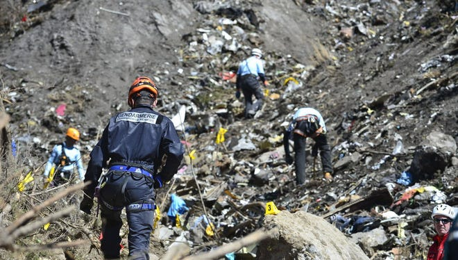 """TOPSHOTS A handout photo taken on March 26, 2015 and released by the French Interior Ministry on March 27, 2015 shows a Gendarme from the Air Transport Gendarmerie (L) working at the crash site of the Germanwings Airbus A320 near Le Vernet, French Alps. The Germanwings co-pilot who flew his Airbus into the French Alps, killing all 150 aboard, hid a serious illness from the airline, prosecutors said on March 27 amid reports he was severely depressed. AFP PHOTO / HO / FRANCIS PELLIER / DICOM / MINISTERE DE L'INTERIEUR == RESTRICTED TO EDITORIAL USE - MANDATORY CREDIT """"AFP PHOTO / FRANCIS PELLIER / DICOM / MINISTERE DE L'INTERIEUR"""" - NO MARKETING - NO ADVERTISING CAMPAIGN - DISTRIBUTED AS A SERVICE TO CLIENTS ==Francis Pellier/AFP/Getty Images ORG XMIT: - ORIG FILE ID: 539240719"""