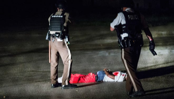 Police come upon a man lying in a parking lot with what appears to be gunshot wounds after a barrage of gunfire erupted in Ferguson, Mo., during a demonstration to mark the one-year anniversary of the shooting of Michael Brown on Aug. 9, 2015.
