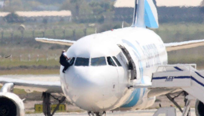 A person believed to be a member of the crew climbs out of a cockpit window of the hijacked EgyptAir A320 plane parked at a sealed off area of the Larnaca Airport, in Larnaca, Cyprus, on March 29, 2016.