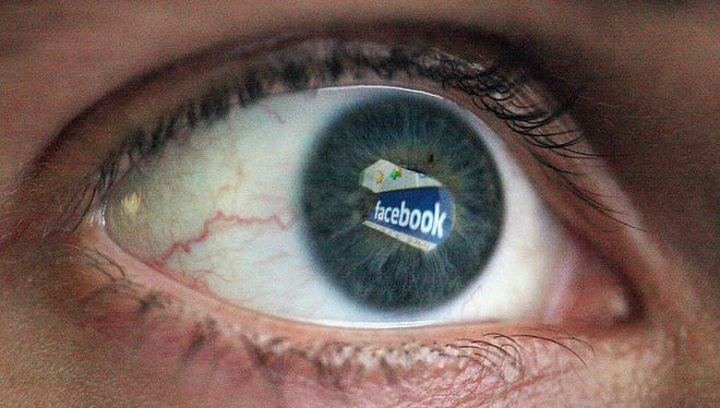 Facebook is reflected in the eye of a man.