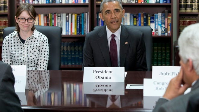 President Barack Obama, joined by Air Force veteran of ten years Michelle Fisher, left, and others, participates in a roundtable about clean energy, Friday, April 3, 2015, at Hill Air Force Base, Utah.