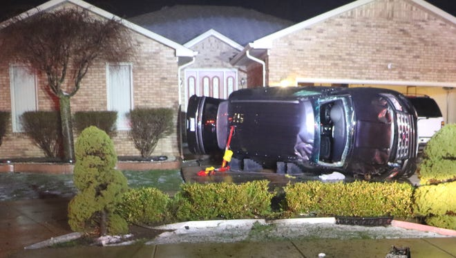 A sport utility vehicle crashed and landed on its side in a driveway in front of a Macomb Township home on Monday, April 11, 2016.