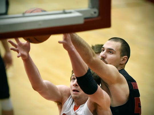 MSU-Moorhead's Isaac Sevlie (left) and St. Cloud State's Nebojsa Stanojevic battle for a rebound under the SCSU basket during the first half Saturday, Feb. 13, at Halenbeck Hall.