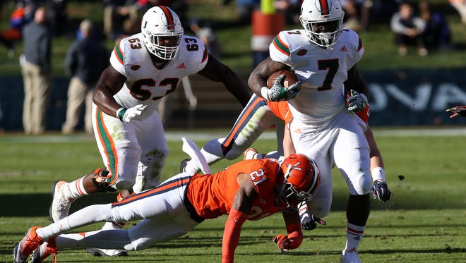 File: Then-Miami Hurricanes running back Gus Edwards (7) carries the ball as Virginia Cavaliers safety Juan Thornhill (21) attempts the tackle in the second quarter at Scott Stadium. The Hurricanes won 34-14. Mandatory Credit: Geoff Burke-USA TODAY Sports