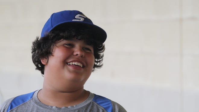 Cincinnati Steam bat boy Omar Mrabet, 12, talks with players in the dugout prior to a game on Tuesday, July 31, 2018.