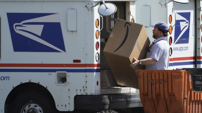 An Amazon package is loaded onto a U.S. Postal Service truck, Tuesday, Aug. 18, 2020, Portland, Maine. Facing public pressure and state lawsuits, the Postmaster general announced Tuesday he is halting some operational changes to mail delivery that critics warned were causing widespread delays and could disrupt voting in the November election.