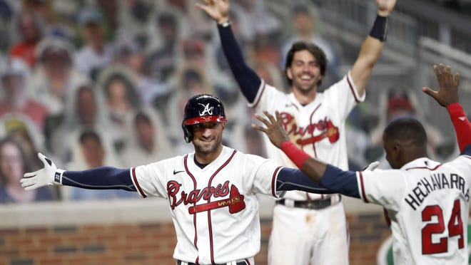 Atlanta Braves' Nick Markakis, left, celebrates with Adeiny Hechavarria (24) after hitting a game-winning home run in the ninth inning of a baseball game against the Atlanta Braves Thursday, Aug. 6, 2020, in Atlanta.