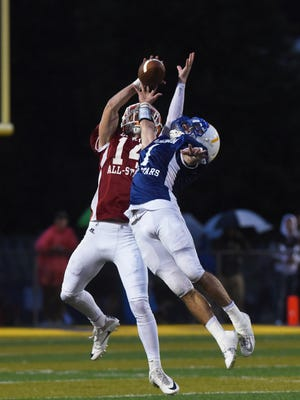 Licking County's Mason Johnson pulls in a pass over a leaping Jacob Mohler of Muskingum Valley during the Muskingum Valley-Licking County All Star Game in Duncan Falls on Friday.