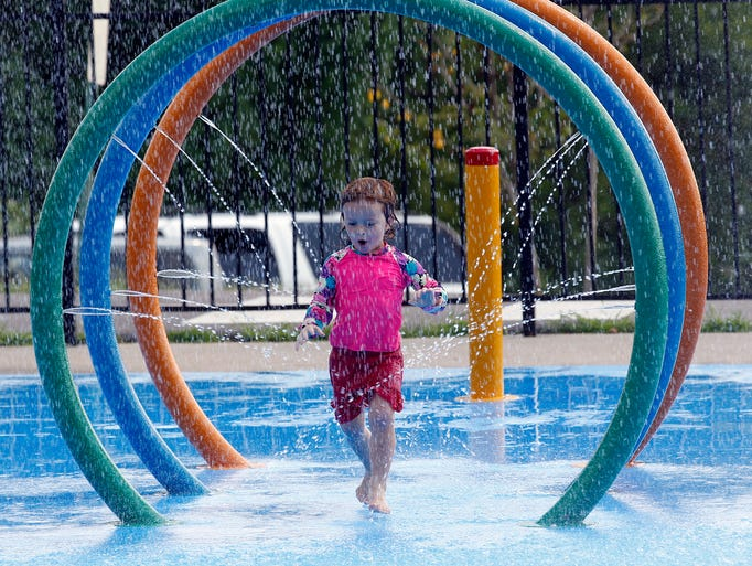 Kezia Williford, 3 makes her way through the spray as she and several other kids had fun enjoying the last days of summer at the Edith Pettus Park & Splash Park on Thursday.