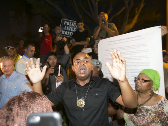 The Rev. Jarrett Maupin (center) speaks to protesters