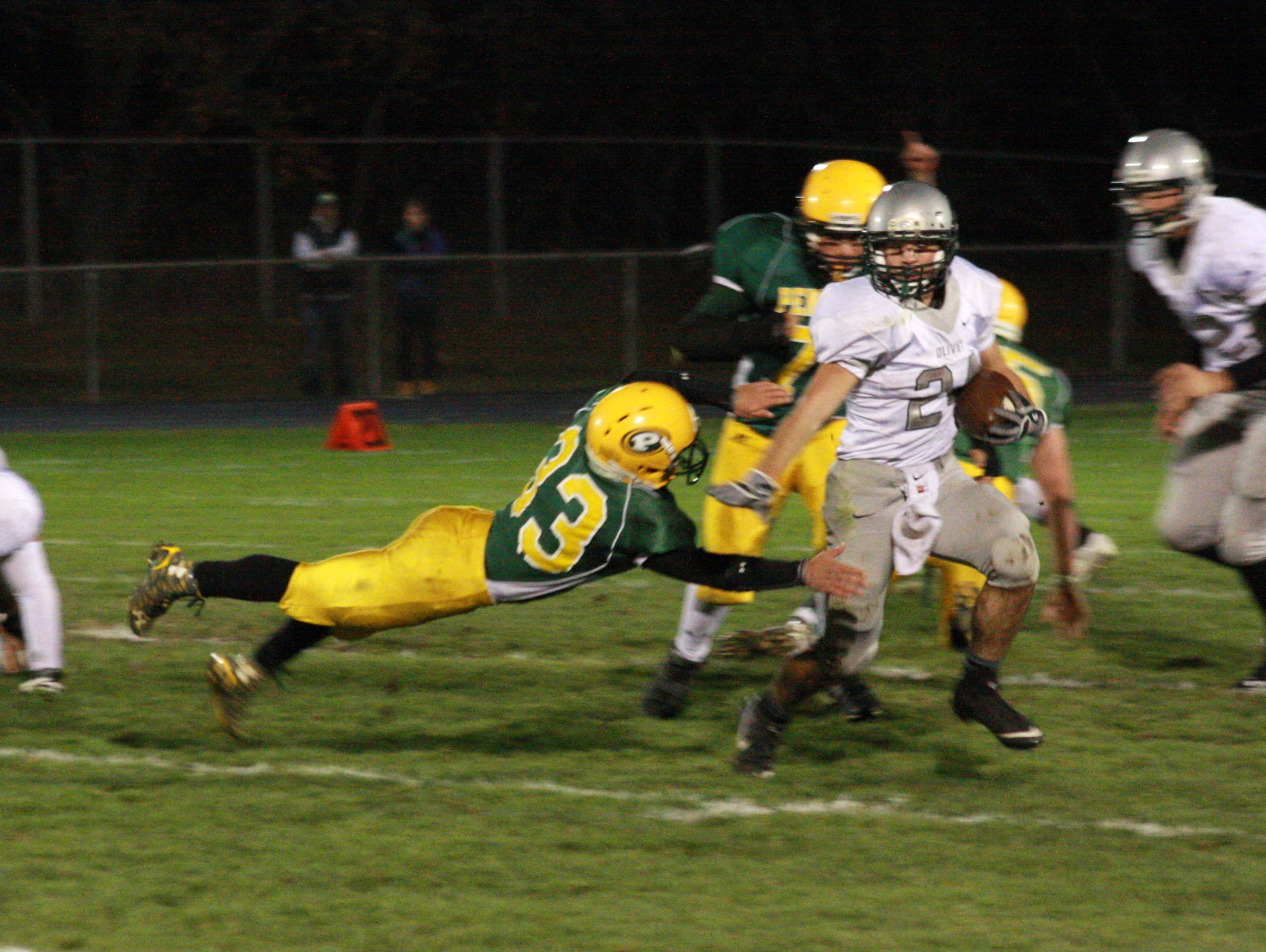 Olivet High School Senior, Chase Martin runs past Pennfield defender, Michael Davis, to score a touchdown during Friday night's game at Pennfield High School